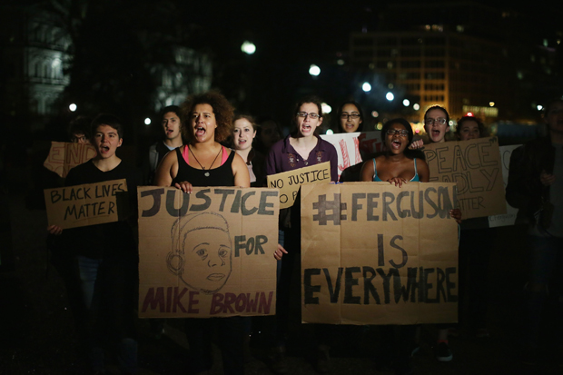 About 100 demonstrators continued to sing, chant and dance in protest outside the White House hours after the Ferguson grand jury decision was announced in Missouri.