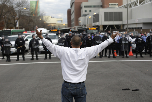 A man who randomly joined demonstrators protesting the shooting death of Michael Brown confronts police officers in riot gear November 30, 2014 in St. Louis, Missouri.