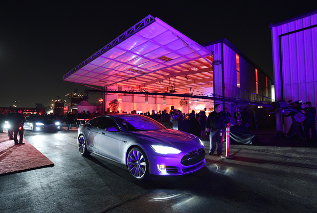 """Tesla owners take a ride in the new Tesla """"D"""" model electric sedan after Elon Musk, CEO of Tesla, unveiled the dual engine chassis of the new Tesla 'D' model, a faster and all-wheel-drive version of the Model S electric sedan, Oct. 9, 2014 in Hawthorne, California. The D will be able to accelerate to 60 miles per hour in just over 3 seconds."""