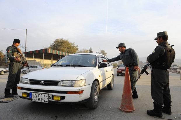 Afghan policemen search a car at a checkpoint in Kabul on November 18, 2013.