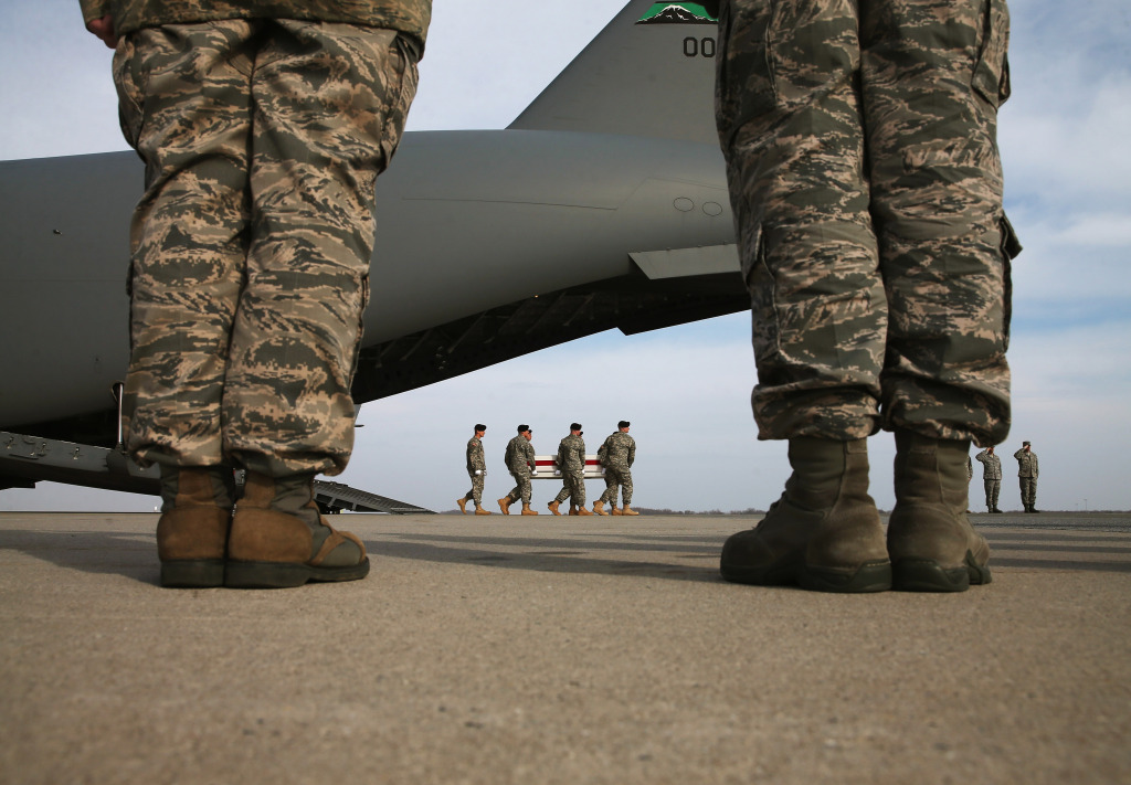 A US Army carry team moves a transfer case   during a dignified transfer at Dover Air Force Base, on December 16, 2014 in Dover, Delaware.