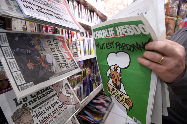 A man displays the latest edition of French satirical magazine Charlie Hebdo shortly after it went on sale on January 14, 2015 in Montpellier, France.