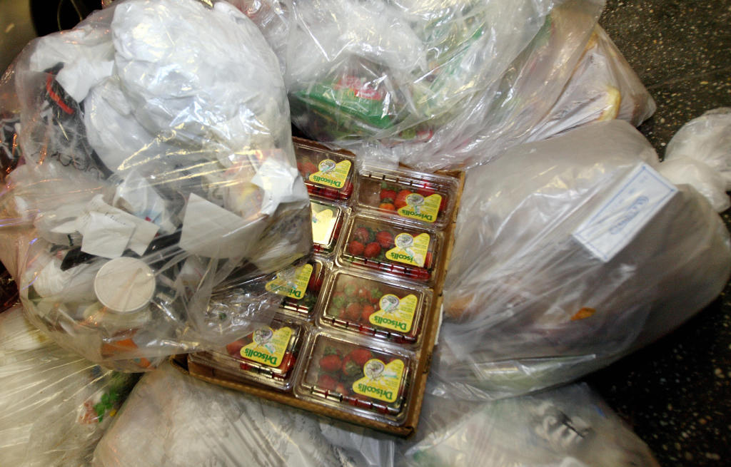 "Boxes of strawberries sit amongst bags of trash found by ""Freegans"" outside of a grocery store in New York."
