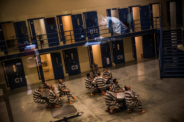 An officer is reflected in the glass as inmates sit in the county jail on July 26, 2013 in Williston, North Dakota.