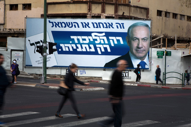 This March 12 photo shows Israelis in Ramat Gan walking by campaign posters showing Israeli Prime Minister Benjamin Netanyahu. Israelis vote March 17 in an election seen as a referendum on Netanyahu's tenure.