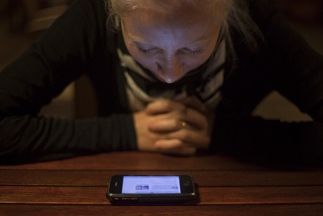 A girl reads the news on a smartphone.