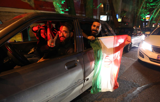 "People flash the ""V for Victory"" sign and hold an Iranian flag out of a car window April 2 as they celebrate on Valiasr street in northern Tehran after the announcement of an agreement on Iran nuclear talks."