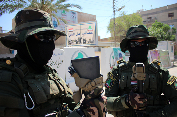 Iraqi fighters of the Shiite militia The League of the Righteous stand guard outside their headquarters  May 18 2015 in Basra, as Shiite militias converged on Ramadi in a bid to recapture it from ISIS.