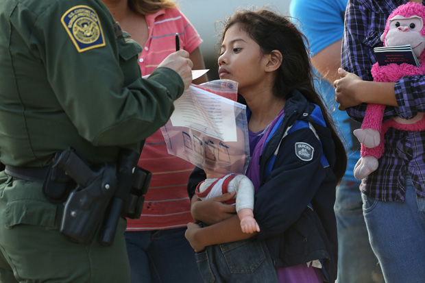 Salvadorian immigrant Stefany Marjorie, 8, watches as a U.S. Border Patrol agent records family information on July 24, 2014 in Mission, Texas.