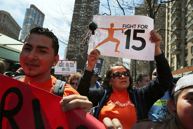 Low wage workers and supporters demand a minimum wage of $15  on April 15 in New York City. This week, Los Angeles joined Seattle and San Francisco in raising the minimum wage to $15.