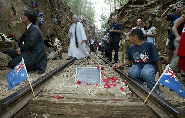 In this 2004 file photo, a pastor crosses a portion of Thailand's infamous Death Railway tracks after a special dawn vigil in Kanchanaburi.