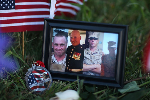 A photograph of the victims is seen among the memorial setup in front of the Armed Forces Career Center/National Guard Recruitment Office  in Chattanooga, Tennessee.