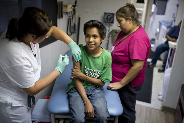 Public school student Julio Valenzuela, 11, smiles as he gets a Measles, Mumps and Rubella vaccination (MMR) at a free immunization clinic for students before the start of the school year,  in Lynwood, California.