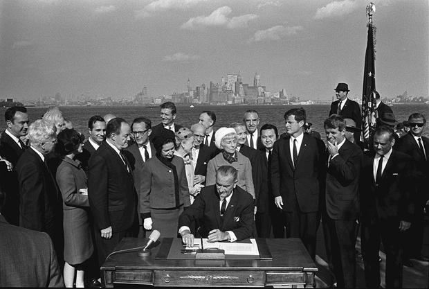 President Lyndon B. Johnson signs the 1965 Immigration Act as Vice President Hubert Humphrey, Lady Bird Johnson, Muriel Humphrey, Sen. Edward (Ted) Kennedy, Sen. Robert F. Kennedy and others look on.