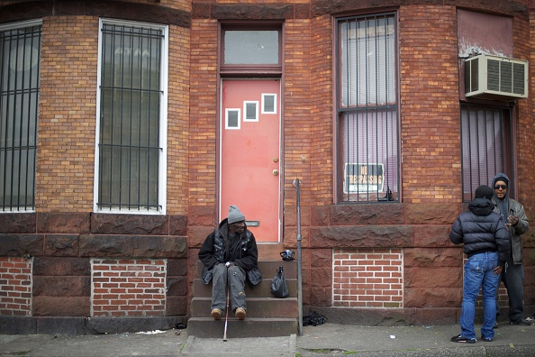 A man sits on fronts steps in a neighborhood near the Western District Police Station after the  death of Freddie Gray in Baltimore, Maryland.