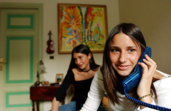 This file photo shows Ludovica Lombardini, 17,  on the phone as her friend Virginia Recchi, 16, waits in the background.