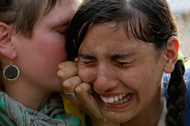 A migrant girl is overcome by pepper spray and tear gas after Hungarian police repelled a Sept. 16 attempt by migrants to break the border post gate and pull down the razor wire fence in Horgos, Serbia.