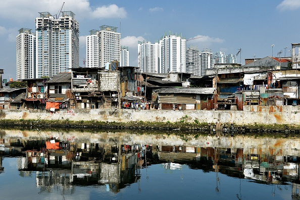 New construction of apartment buildings is the backdrop for shanty houses in downtown Jakarta in a photo taken in July.