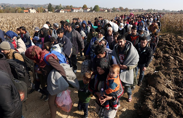 Migrants and refugees who spent the night outdoors are escorted by Slovenian soldiers and police officers as they walk towards a refugee camp after crossing the Croatian-Slovenian border near Rigonce, Slovenia, on Monday.