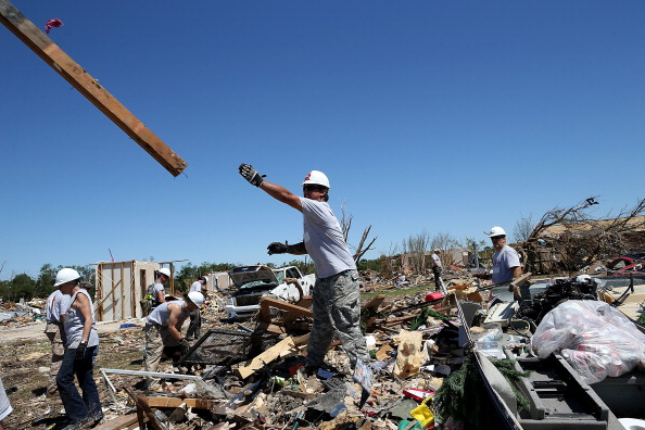 Workers with Team Rubicon sift through the remains of a home that was damaged by a tornado on June 2, 2013 in Moore, Oklahoma. Team Rubicon is an aid organization that unites military veterans with emergency first responders.