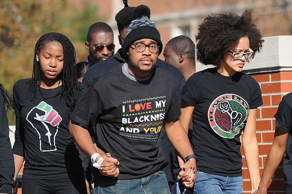 Jonathan Butler, a University of Missouri grad student who did a seven-day hunger strike, is greeted by a crowd of students Monday on campus after Tim Wolfe resigned as university president.