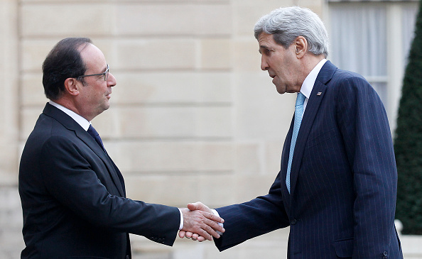 French President Francois Hollande welcomes Secretary of State John Kerry, left, prior to a meeting at the Elysee Presidential Palace in Paris on Tuesday.