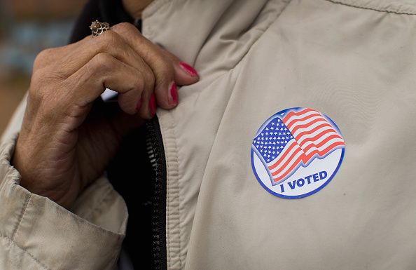 """A voter shows off her """"I Voted"""" sticker as she leaves a polling place on Nov. 4, 2014, in Ferguson, Missouri."""