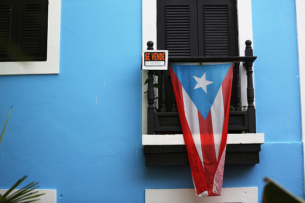 A for sale sign is seen hanging from a balcony next to a Puerto Rican flag in San Juan, Puerto Rico in July 2015.
