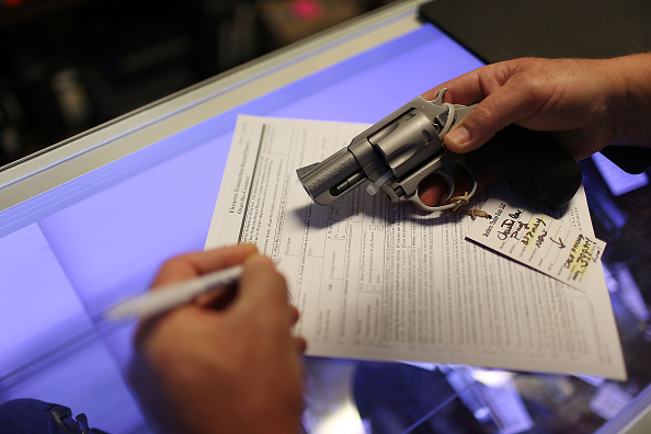 Mark O'Connor fills out his federal background check paperwork as he purchases a handgun at the K&W Gunworks store in Delray Beach, Florida, on Jan. 5, the day President Obama announced executive actions on gun control.