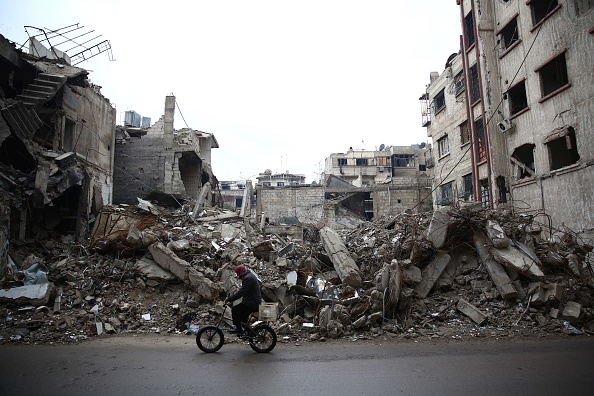 A man rides a bicycle past the rubble of a destroyed building in the rebel-held town of Douma, on the eastern edges of the Syrian capital Damascus, on January 5.