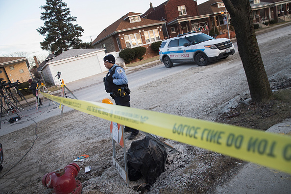 A Chicago police officer guards the perimeter of a crime scene where six people were found slain inside a home on the city's Southwest Side on February 4 in Chicago, Illinois. Last month Chicago recorded 51 homicides, the highest toll for the month since at least 2000.