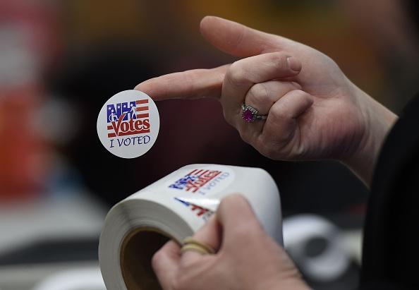 An election worker hands out stickers to voters after casting their ballots at Belmont High School February 9 in Belmont, New Hampshire.