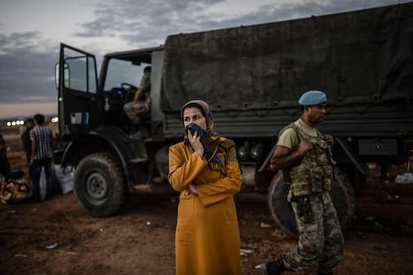 A Syrian Kurdish woman stands in front of military truck after crossing the border between Syria and Turkey after several mortars hit both sides near the southeastern town of Suruc in Sanliurfa province on September 29, 2014.