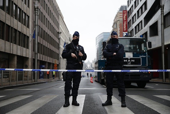 Belgian police officers stand guard near Maelbeek - Maalbeek subway station  in Brussels on March 23, a day after triple bomb attacks in the Belgian capital killed about 35 people and left more than 200 people wounded.