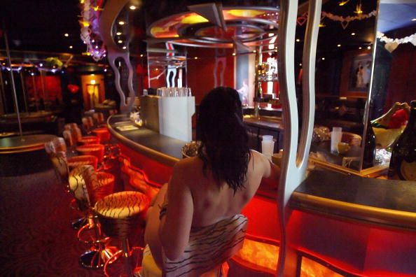 A sex worker poses at the bar of Berlin's Artemis brothel May 4, 2006. Artemis, the largest brothel in Berlin, boasts 4 stories, 70 rooms, 3 saunas, 2 small movie theaters, a pool and a fitness center.