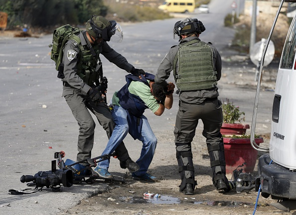 Israeli border guards aggress a journalist during clashes between Palestinian demonstrators and Israeli security forces at the entrance of the Palestinian town of Al-Bireh on the outskirts of Ramallah in the Israeli-occupied West Bank, on October 30, 2015.
