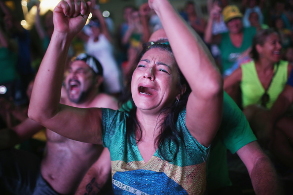 A supporter of the impeachment of Brazilian president Dilma Rousseff dressed in national colors cheers while watching a live television broadcast as lower house deputies cast their votes in the impeachment process on April 17 in Rio de Janeiro, Brazil.