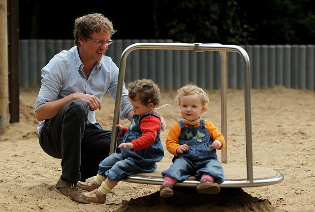This 2010 photogrpah shows Oliver H., 42, a married federal employee on six-month paternity leave, playing with his twin 14-month-old daughters Lotte (L) and Alma at a playground  in Berlin, Germany.