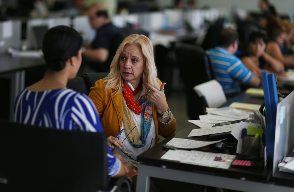 Maria Elena Santa Coloma,(R) an insurance advisor with UniVista Insurance company, helps Shessy Gonzalez sign up for a health plan under the Affordable Care Act, also known as Obamacare, on December 15, 2015 in Miami, Florida.