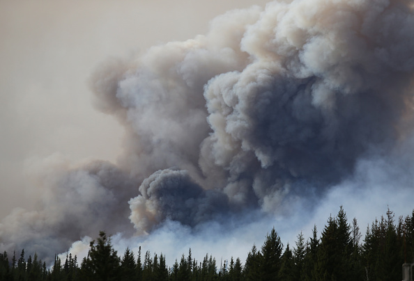 Flames rise off Highway 63 on May 7 outside Fort McMurray, where raging forest fires forced more than 88,000 from their homes.
