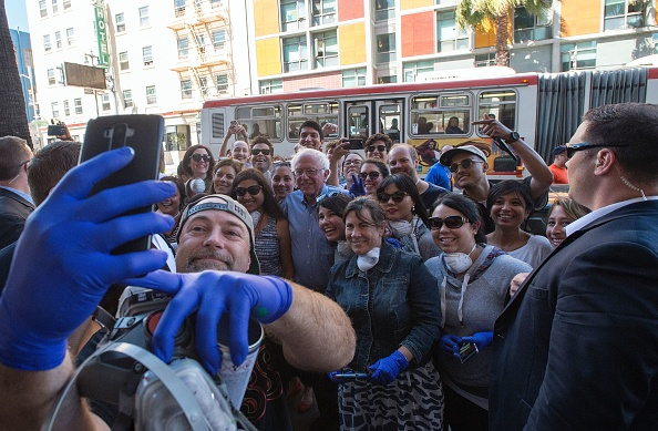 Democratic presidential candidate Bernie Sanders poses for a photo with a group of street artists during a walk through San Francisco, California on May 18.
