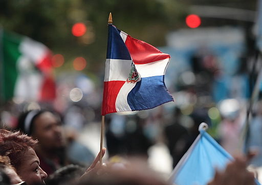 A parade attendee waves a Dominican flag at NYC's 2007 Hispanic Day Parade.