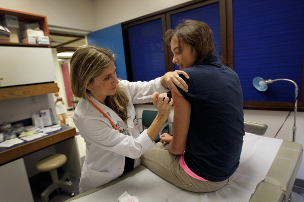 University of Miami pediatrician Judith L. Schaechter, M.D. (L) gives an HPV vaccination to a 13-year-old girl in her office at the Miller School of Medicine on September 21, 2011 in Miami, Florida.