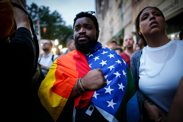 A man holds a flag during a vigil June 13 in solidarity for the victims killed at Pulse nightclub in Orlando in New York on June 13, 2016.