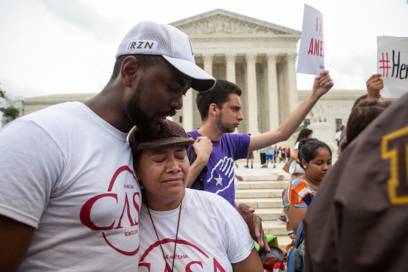 Rosario Reyes, an undocumented mother from El Salvador, reacts to news on a Supreme Court decision blocking Obama's immigration plan, which would have protected millions of immigrants from deportation, in front of the U.S. Supreme Court, on June 23 in Washington, DC. The court was divided 4-4, leaving in place an appeals court ruling blocking the plan.