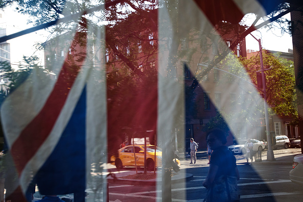 A British flag hangs in the window of Myers of Keswick, a British grocery store, June 24 in New York City.