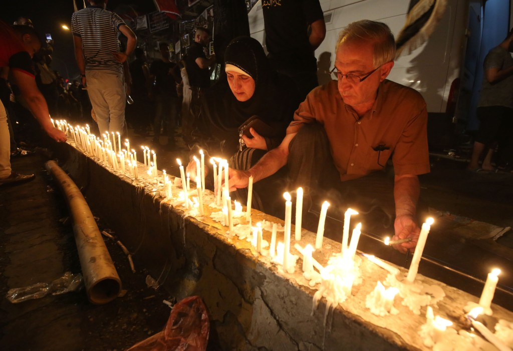 Iraqis light candles on July 5 at the site of a suicide car bomb attack which took place early on July 3 in Baghdad's Karrada neighborhood killing at least 213 people and wounding more than 200.