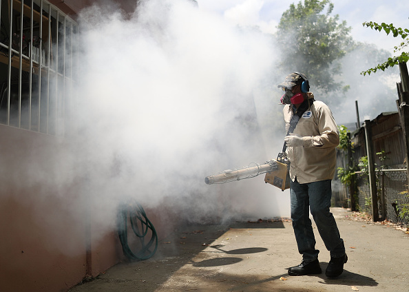 Carlos Varas, a Miami-Dade County mosquito control inspector, uses a Golden Eagle blower to spray pesticide to kill mosquitos in the Wynwood neighborhood as the county fights to control the Zika virus outbreak on August 2 in Miami, Florida.