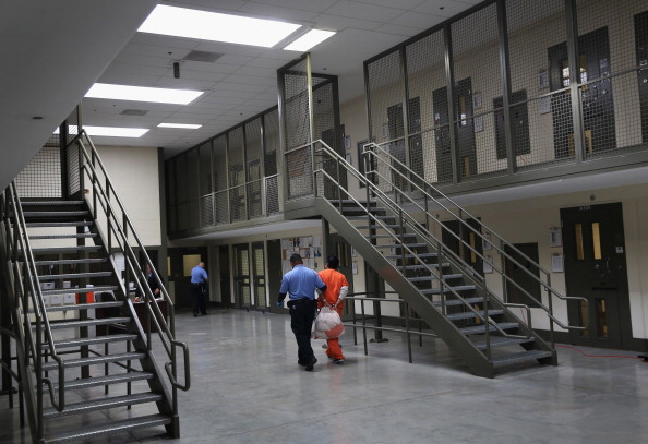 A guard escorts an immigrant detainee on November 15, 2013 at California's Adelanto Detention Facility, managed by the private GEO Group. While the U.S. Department of Justice said last week that it will move away from privately managed prisons, the Department of Homeland Security has not announced any plans to phase out those companies' role in immigration control.