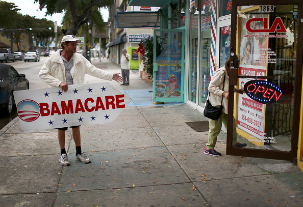Pedro Rojas holds a sign directing people to an insurance company where they can sign up for the Affordable Care Act, also known as Obamacare, on February 5, 2015 in Miami, Florida.